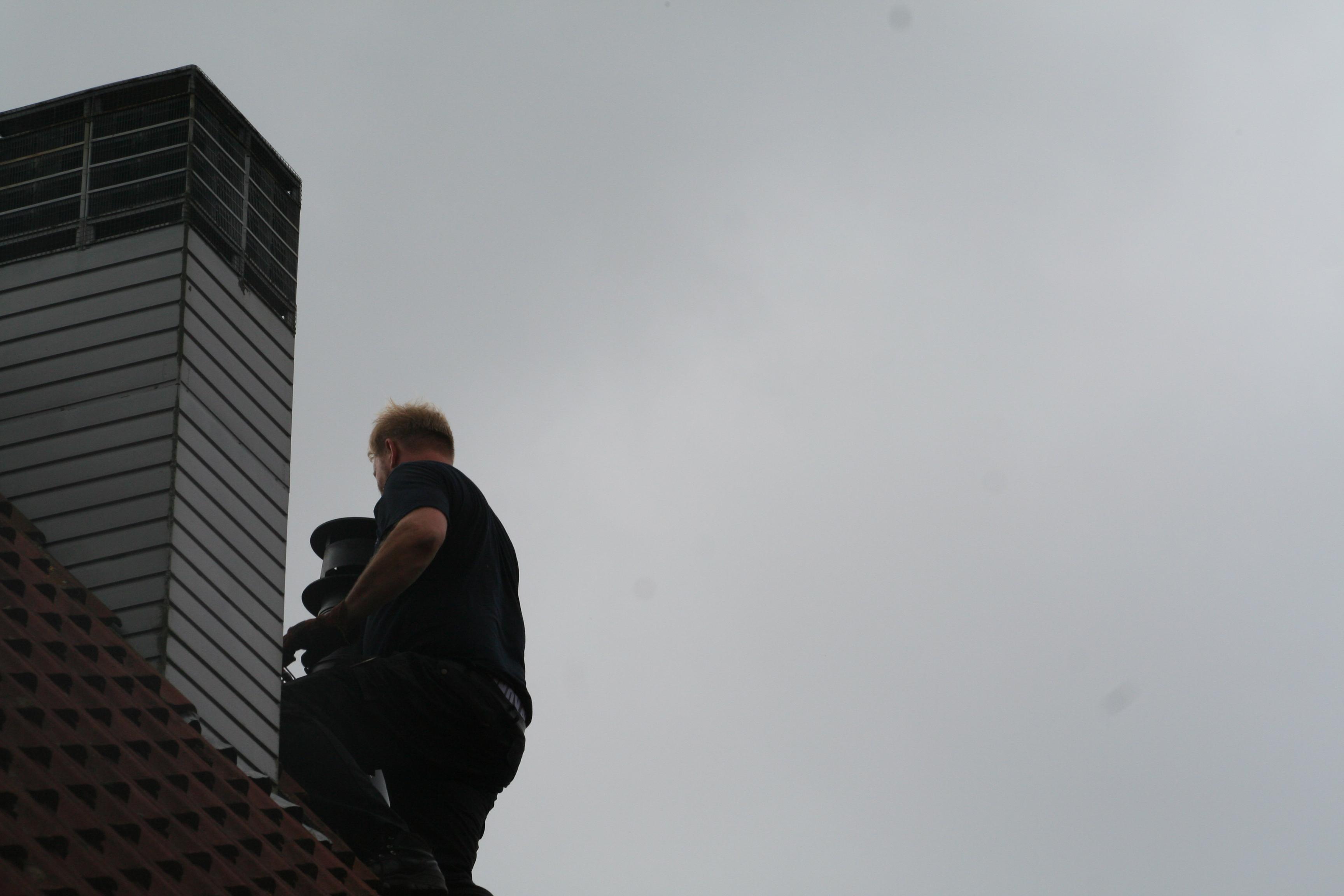 Jelte Hoekstra veegt een schoorsteen vanaf het dak